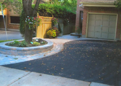 Asphalt driveway with detailed interlock flower bed and pathway