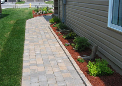 Interlocking brick walkway with flower bed